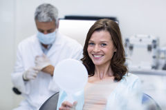 Patient checking her teeth in mirror Royalty Free Stock Photo