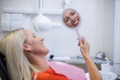 Patient checking her teeth in mirror Stock Photography