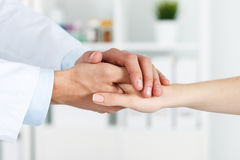 Patient cheering and support. Friendly male doctor's hands holding female patient's hand for encouragement and empathy. Partnership, trust and medical ethics Stock Photography