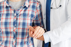 Patient cheering and support. Friendly male doctor's hands holding female patient's hand for encouragement and empathy. Partnership, trust and medical ethics Royalty Free Stock Photo