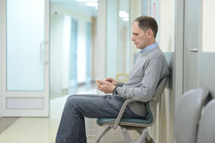 Patient in a clinic. Patient with smartphone waiting for the doctor appointment in the clinic Royalty Free Stock Photos