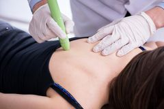 The patient in clinic undergoing laser scar removal. Patient in clinic undergoing laser scar removal stock photos