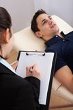 Patient communicating while psychologist writing notes. Male patient communicating while psychologist writing notes on clipboard in clinic Royalty Free Stock Image