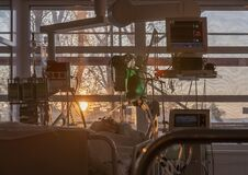 Patient connected to medical ventilator, and to monitor in ICU in hospital,  the windows sun rises