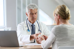 Patient consulting doctor at his office royalty free stock images