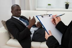 Patient On Couch And Psychiatrist Writing On Clipboard. African Patient Sitting On Couch And Female Psychiatrist Writing On Clipboard Stock Photography