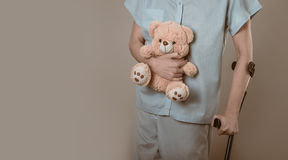 Patient on crutches with a children's toy.  Royalty Free Stock Photography