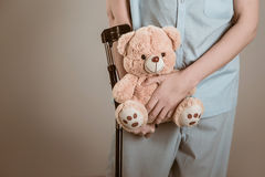 Patient on crutches with a children's toy Royalty Free Stock Photos