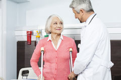Patient With Crutches Looking At Doctor In Rehab Center. Senior female patient with crutches looking at doctor in rehab center Royalty Free Stock Photography