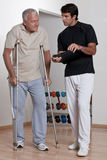 Patient on Crutches and Physician. Patient on crutches discusses his progress Stock Photos