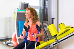 Patient with crutches sitting on weight machine. Smiling beautiful female patient with crutches sitting on weight machine in physical therapy gym Royalty Free Stock Photos