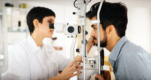 Patient or customer at slit lamp at optometrist or optician Royalty Free Stock Image