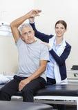 Patient d'Assisting Senior Male de physiothérapeute à exercer Photographie stock