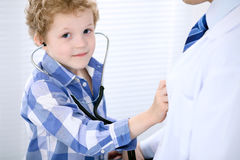 Patient d'enfant examinant son docteur par le stéthoscope Photos libres de droits