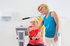 Patient de aide d'entraîneur avec la machine d'exercice Images stock