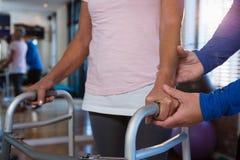 Patient de aide de physiothérapeute à marcher avec le cadre de marche Photo stock