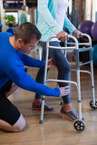 Patient de aide de physiothérapeute à marcher avec le cadre de marche Photographie stock
