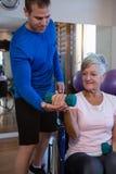 Patient de aide de physiothérapeute masculin en exécutant l'exercice avec l'haltère Photo stock