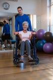 Patient de aide de physiothérapeute masculin en exécutant l'exercice avec l'haltère dans la clinique Photographie stock