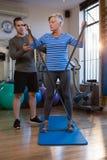 Patient de aide de physiothérapeute masculin en exécutant l'exercice avec la bande de résistance Photos stock