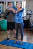 Patient de aide de physiothérapeute masculin en exécutant l'exercice avec la bande de résistance Photo libre de droits
