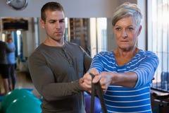 Patient de aide de physiothérapeute masculin en exécutant l'exercice avec la bande de résistance Image libre de droits