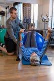 Patient de aide de physiothérapeute masculin en exécutant l'exercice avec la bande de résistance Images stock