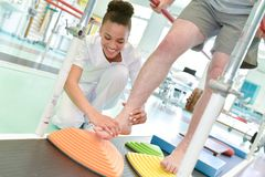 Patient de aide de médecin féminin à marcher sur le tapis roulant Images stock
