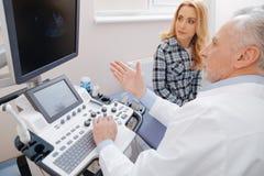 Patient de consultation de docteur compétent dans la clinique Photographie stock libre de droits
