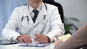 Patient de consultation de médecin, écrivant des symptômes, prescription de lecture de femme photographie stock libre de droits