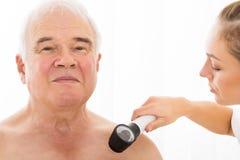 Patient de docteur Examining Skin Of avec Dermatoscope Image stock