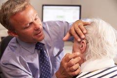 Patient de docteur Fitting Senior Female présentant la prothèse auditive Images stock
