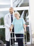 Patient de docteur Helping Senior Female avec Walker In Fitness Stud Photo stock