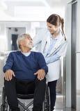 Patient de docteur Looking At Senior sur le fauteuil roulant Image libre de droits