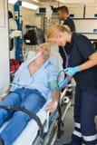 Patient de examen d'équipe paramédicale sur la civière Images libres de droits