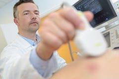 Patient de examen de docteur sur l'echograph Image stock