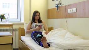 Patient de jeune fille présentant la jambe blessée utilisant le téléphone dans une chambre d'hôpital se trouvant sur le lit banque de vidéos