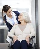 Patient de Looking At Senior de physiothérapeute s'asseyant dans le fauteuil roulant Photos libres de droits