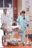 Patient de roulement de personnel médical sur le lit avec l'égouttement et le moniteur image stock