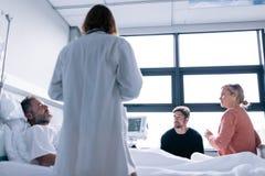 Patient de visite de médecin féminin dans la chambre d'hôpital Photo stock