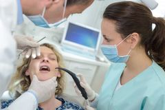 Patient dentist and assistant in office dental clinic. Patient dentist and assistant in office of a dental clinic Stock Images
