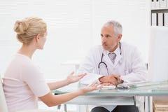 Patient, der einen ernsten Doktor konsultiert Stockbild
