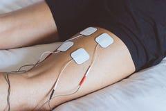 Patient, der elektrische Anregungstherapie auf Bein anwendet elektrisch lizenzfreies stockfoto