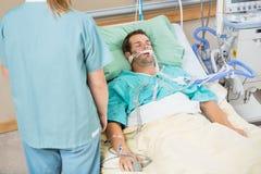 Patient, der mit Krankenschwester Standing By schläft Lizenzfreie Stockfotografie