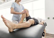Patient an der Physiotherapie, die körperliche Bewegungen mit seinem Therapeuten tut stockfoto
