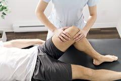 Patient an der Physiotherapie, die körperliche Bewegungen mit seinem Therapeuten tut lizenzfreie stockbilder