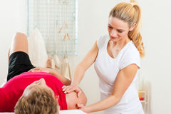 Patient an der Physiotherapie, die Physiotherapie tut Stockfotografie