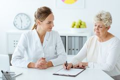 Patient with diabetes and dietician. Patient with diabetes writing daily eating habits during a meeting with dietician Stock Images