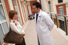 Patient, doctor conversation. A young woman and a male doctor stand outside a building, having a conversation stock photo