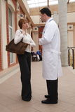 Patient and doctor conversation. A young woman and a male doctor stand outside a building, having a conversation royalty free stock photo